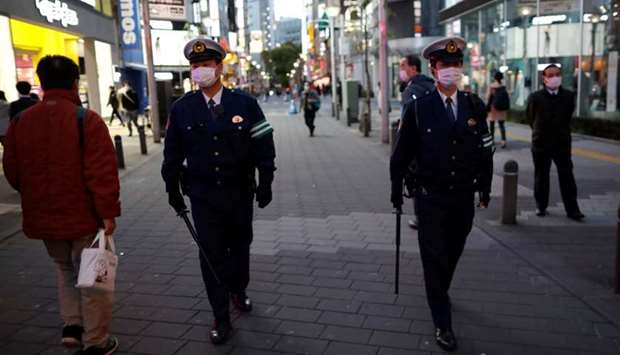 Police officers in Tokyo wearing protective face masks patrol on the street after the government ann