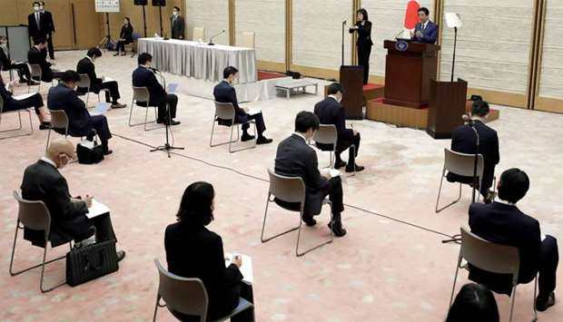 Japan's Prime Minister Shinzo Abe (top R) speaks during a press conference at the prime minister's o