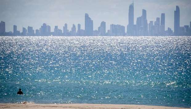 A lone swimmer is seen at Coolangatta Beach with Surfers Paradise in the background, on the Queensla