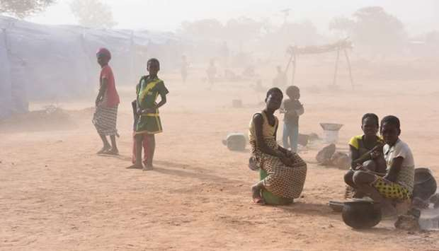 Displaced people, who fled from attacks of armed militants in Roffenega, are engulfed in dust as the