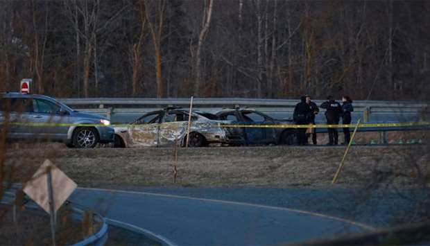RCMP officers go over a car collision scene involving the fake RCMP car driven by Gabriel Wortman in