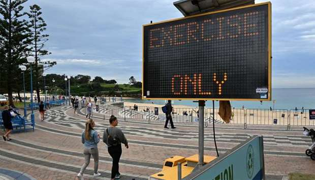 "People walk past a sign reading ""exercise only"" at Coogee Beach in Sydney"