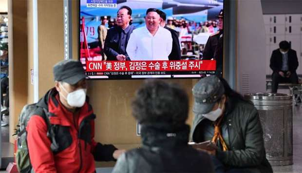 People watch a television news broadcast showing file footage of North Korean leader Kim Jong Un, at