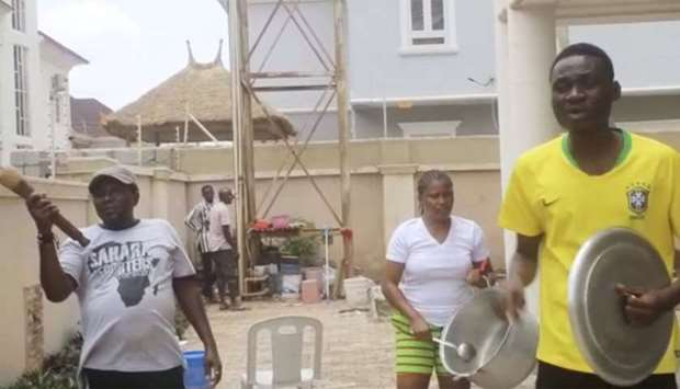 People bang pots and pans in protest over the scarcity of food amid the Nigeria's lockdown to fight