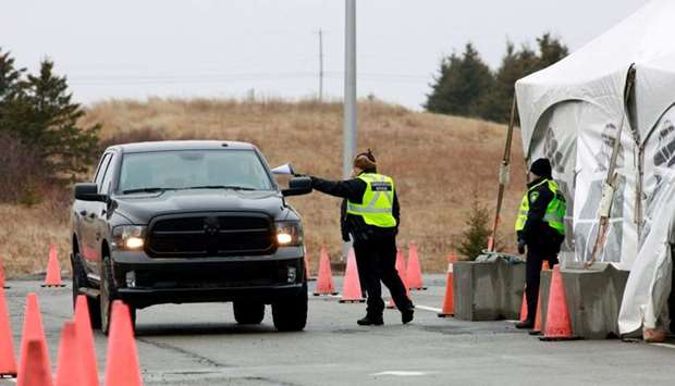 A Nova Scotia conservation officer passes a paper to a person crossing into the province from New Br