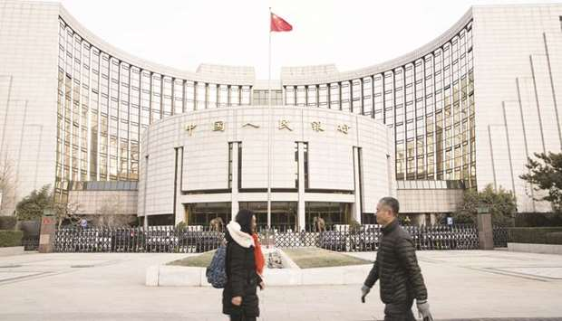 Pedestrians walk past the People's Bank of China headquarters in Beijing. The Chinese central bank s