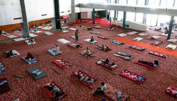 Migrant workers and homeless people rest inside a sports complex turned into a shelter, during a 21-