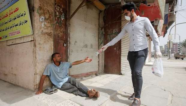 An Iraqi man wearing a protective face mask and gloves gives a bottle of water to a homeless man, wh