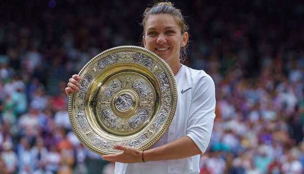 In this July 13, 2019 picture, Simona Halep poses with the winner's trophy after winning at Wimbledo