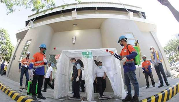 Government officials inspect a disinfection booth at the Ninoy Aquino Stadium, one of the quarantine