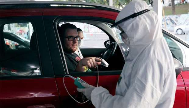 A nurse measures the oxygen level of the blood of a man during drive-thru triage to identify people