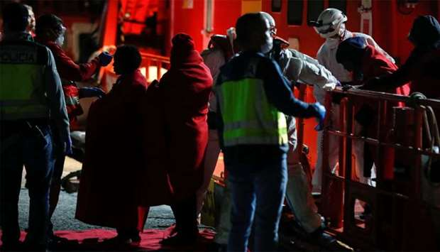 Red Cross members take temperature of migrants before disembarking from a Spanish coast guard vessel