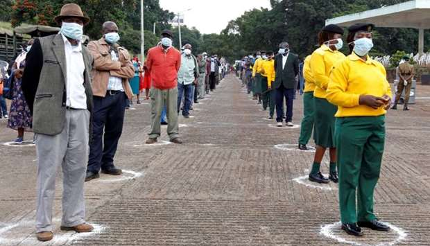 Workers of the Nairobi City County Government queue while observing social distancing to collect let