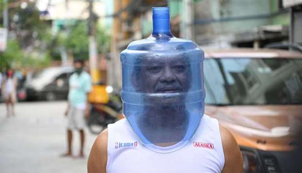 A resident using an improvised face shield made from a plastic water tank to protect him from the CO