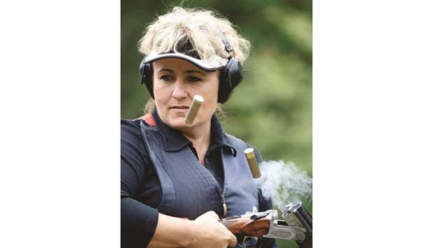 Hungarian skeet shooter Diana Igaly empties shell casings from her gun during a practice session in