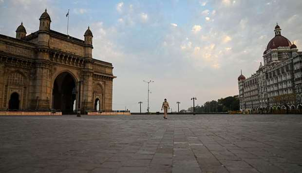 A policewoman walks through a deserted area between the Gateway of India and Taj Mahal Hotel ahead o