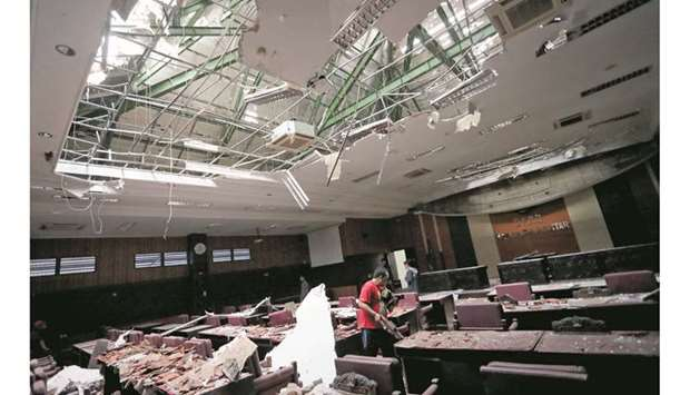 A man cleans up a damaged courtroom affected by an earthquake of magnitude 6.0 struck in the ocean 9