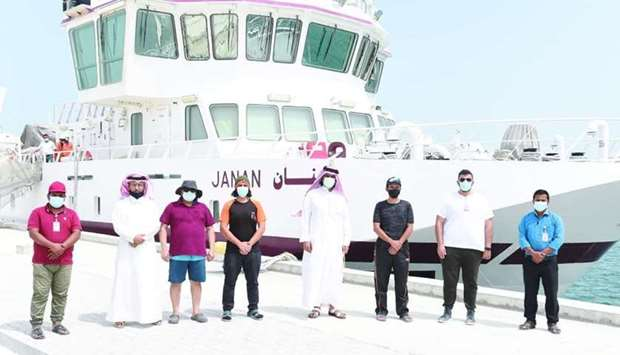 Some of the team members pose in front of the research vessel Janan.