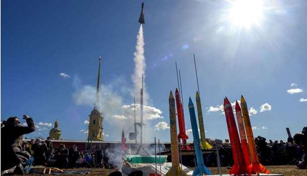 Bystanders watch launch of model rockets near The Peter and Paul Fortress in Saint Petersburg, durin