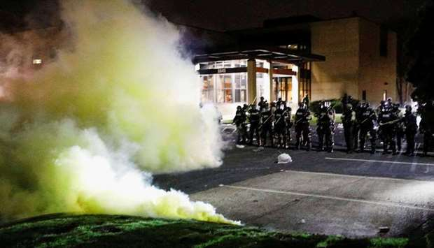 Tear gas is seen as officers stand guard outside Brooklyn Center Police Department with trash thrown