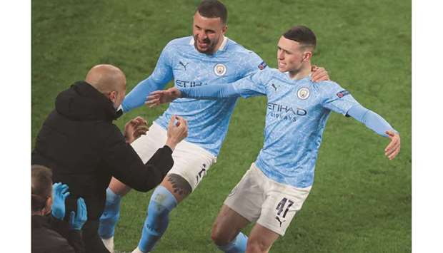 Manchester City's Phil Foden (right) celebrates scoring a goal with teammate Kyle Walker (centre) an