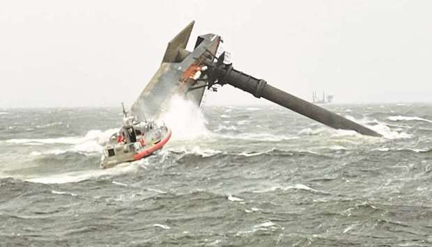 A Coast Guard Station Grand Isle boat heads toward a capsized commercial lift boat while searching f