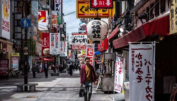 A man walks in the Dotonbori area of Osaka, Japan, as record numbers of new Covid-19 infections were