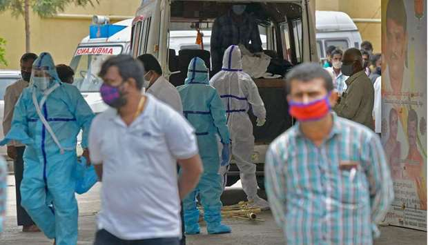 Family members, with help from the municipal staff transfer the bodies of the patients who died of t