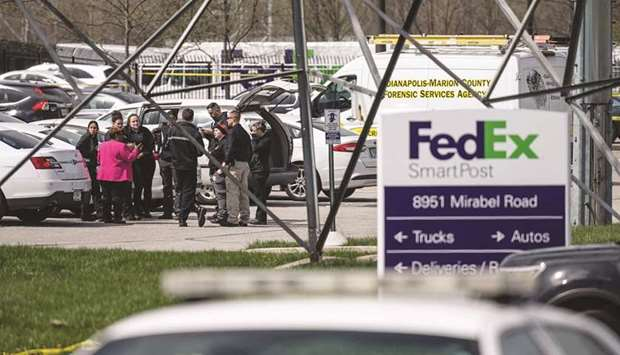 A group of crime scene investigators gather to speak in the parking lot of a FedEx SmartPost buildin