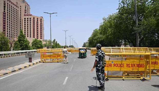 Police personnel stop vehicles at a checkpoint during a weekend lockdown imposed by the government a