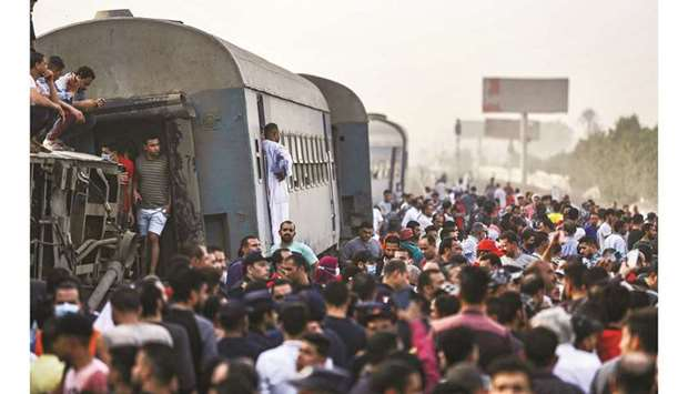 People gather by an overturned train carriage at the scene of a railway accident in the Egyptian cit