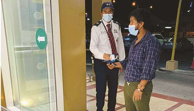 Checking of temperatures and Ehteraz mobile app (green code) at a LuLu store.