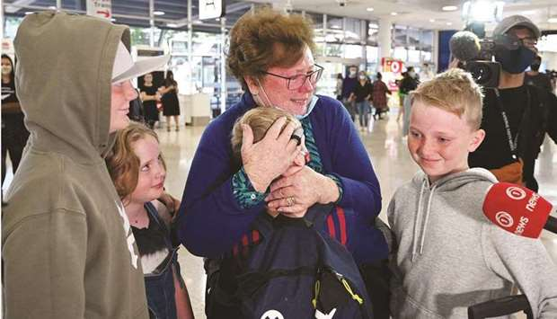 A woman hugs her family members upon their arrival from New Zealand at Sydney International Airport