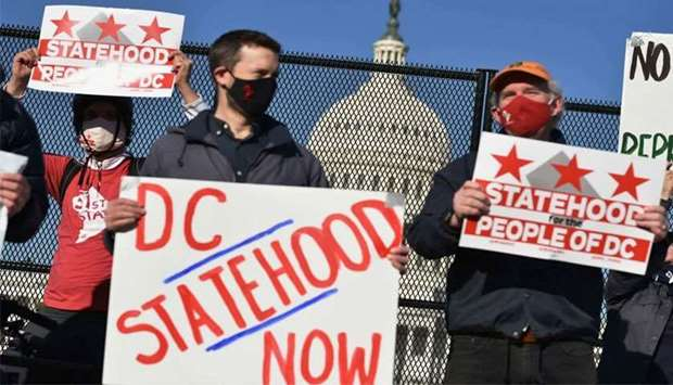 (File photo) Activists hold signs as they take part in a rally in support of DC statehood near the U