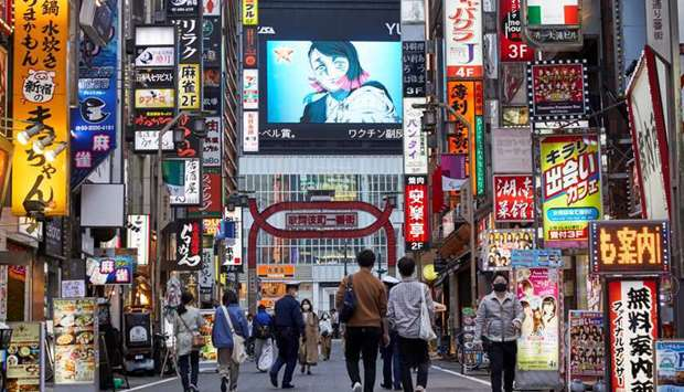 Passersby wearing protective masks stroll through Kabukicho entertainment district during the Covid-