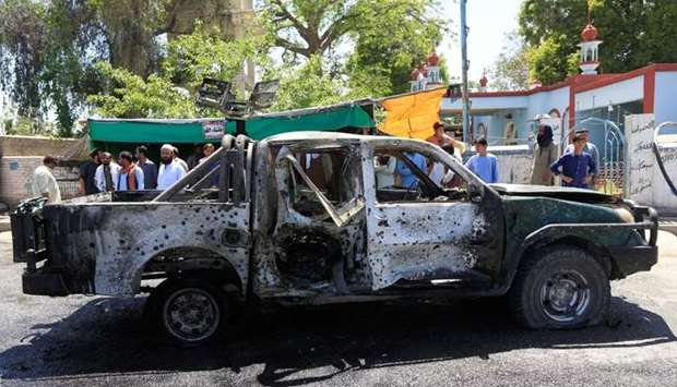 People look at a damaged police vehicle after a blast on April 24, in Jalalabad, Afghanistan