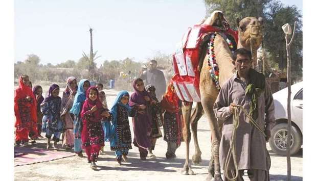 Children follow Roshan the camel, which is carrying  books to them in Mand, Pakistan.