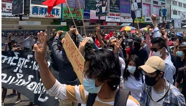Protesters hold up the three finger salute as they take part in a demonstration against the military