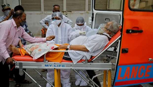 A patient wearing an oxygen mask is wheeled inside a COVID-19 hospital for treatment, amidst the spr