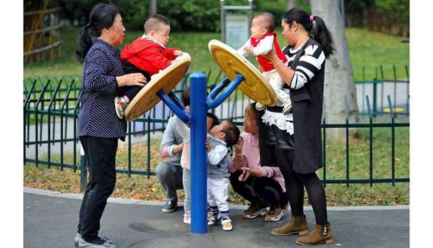 Women play with children at a park in Jinhua, Zhejiang province, China. (Reuters)