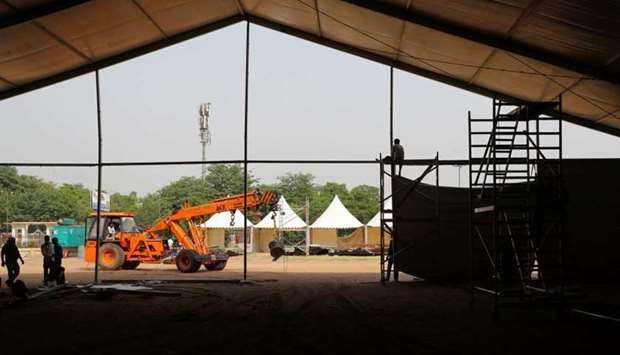 Labourers build a temporary COVID-19 care facility, at Ramlila grounds, amidst the spread of the cor