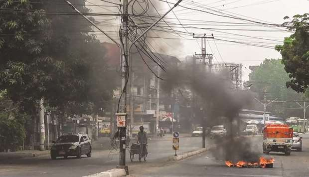 Motorists pass a burning makeshift barricade, erected by protesters demonstrating against the milita