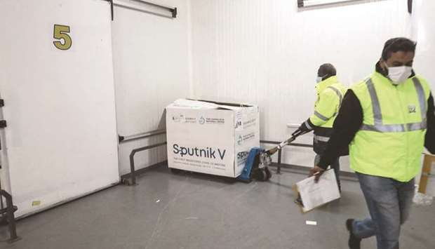Workers handle boxes of the newly-received first batch of the Russian Sputnik V vaccine against the