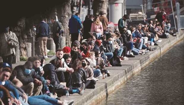 FLIP SIDE: People enjoying a sunny spring day along the banks of the canal Saint-Martin, as France