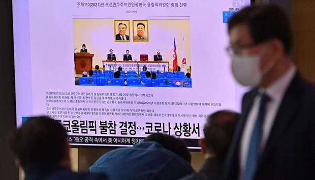 People watch a television screen showing a news report about North Korea's decision not to participa