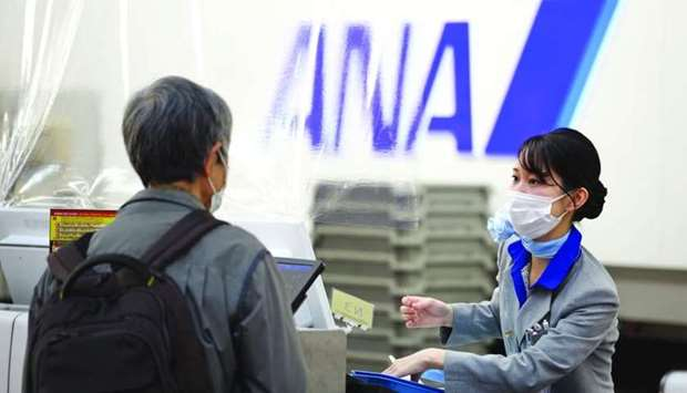 An All Nippon Airways Co (ANA) employee assists a passenger at a check-in counter at Haneda Airport