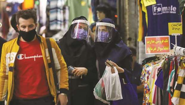 Iranian women wear protective face shields and masks as they walk in Tehran Bazaar, yesterday.
