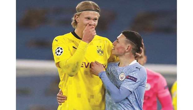 Borussia Dortmund's Erling Braut Haaland (left) talks to Manchester City's Phil Foden after the Cham