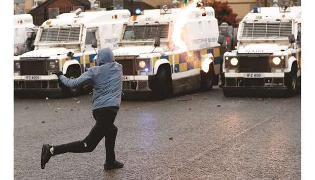 A rioter throws a Molotov cocktail at the police on the Springfield Road as protests continue yester