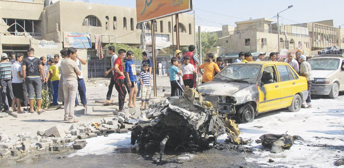 Residents gather at the site of a car bomb attack in Baghdad's Hurriya district yesterday.